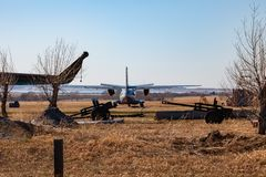 A small aircraft for the transport of passengers and paratroopers is behind the fence among the rarities of artillery guns and stock photo