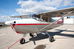 Small airplane. A Cessna 172 tied down at the airport.  Beautiful blue sky with white clouds make a perfect day to be flying Royalty Free Stock Photography
