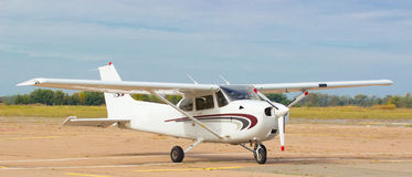 Small airplane in dirt airfield Royalty Free Stock Photo