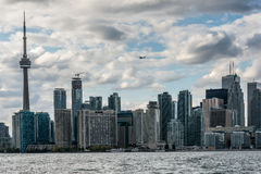 A small airplane flies above the skyscrapers of Old Toronto