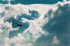 Small airplane. In flight under a cloudy summer sky stock image