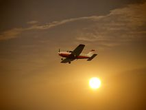 Small Airplane Flying. Small red and white airplane flying in a dusky orange-yellow sky, with a background of sun and clouds stock photography