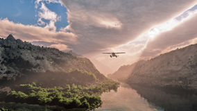 Small airplane flying through snow mountain valley with river. Royalty Free Stock Photo