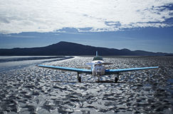 Small Airplane on Heavily Textured Beach Stock Photo