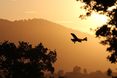 A small airplane landing at sunset. A small yellow airplane is landing in a golden sunset at a mountain airport royalty free stock photography