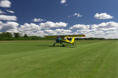 Small airplane landing or taking off on a grass air strip with motion blur to convey movement. Small bush-plane landing on a remote airstrip Royalty Free Stock Photo