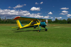 Small airplane landing or taking off on a grass air strip with motion blur to convey movement. Small bush-plane landing on a remote grass airstrip Royalty Free Stock Images