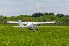 Small airplane. Small white airplane on the green field Stock Image