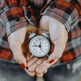 Small alarm clock in female hands Stock Image