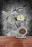 Small alarm clock in meat grinder on grunge monochrome backgroun Stock Photo