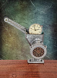 Small alarm clock in meat grinder on grunge scratched background Stock Photography