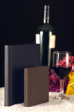 Small Albums with Wine glass. 2 small albums; one leather bound, one cloth with wine glass and bottle. flowers in the background Royalty Free Stock Photo