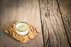 Small alcohol glass with plate on a wooden table background. royalty free stock images