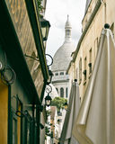 A small alley in Montmartre with the church of Sacre Coeur in ba Royalty Free Stock Images