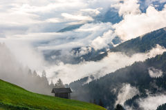 Small alpine house in green forest mountains Stock Images