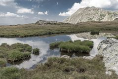 Small alpine lake among white summer clouds. In Retezat Mountains, Romania Stock Image