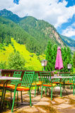 Small Alpine restaurant with Alps, Austria. Small Alpine restaurant on the terrace on the background of the Alps, Austria Royalty Free Stock Photos