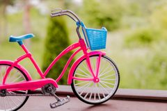Small pink bicycle model on the handrail with garden background.Green transport.Vintage bicycle,selective and soft focus. Small aluminum bicycle model on the stock photos