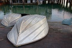 Small aluminum boats or dinghies pulled up on concrete ramp Stock Photos