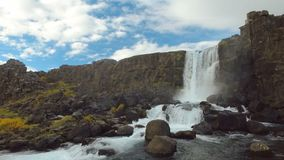 Small amazing waterfall Oxararfoss and river in Iceland at tectonic plate fracture in autumn stock footage