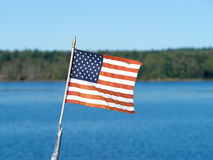 Small American flag with ocean and shore Royalty Free Stock Photos