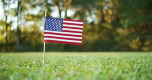 Small American, US or USA, flag waving in the wind outside in the grass