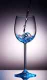 Small amount of transparent liquid in wine glass Royalty Free Stock Photos