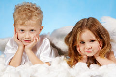 Small angels. Small boy and girl in angelic costume lying on white cloud Stock Image