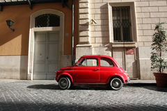 Small Antique Car parked on cobble stone road stock images