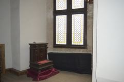Small antique furniture. And stained glass window, in the Corvin Castle, Hunedoara, Transylvania, Romania Stock Photos