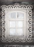 A small antique rustic window. With carvings in a wooden wall in black and white format royalty free stock photos