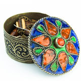 Small antique Tunisian jewel casket. A small round metal jewel casket with an antique look. The colored lit is taken off revealing som jewels inside Stock Photography