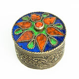 Small antique Tunisian jewel casket. A small round metal jewel casket with an antique look. The colored lit is seen from the top Royalty Free Stock Photos