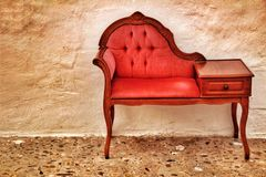 Small and antique vintage red divan in cobblestone street royalty free stock images