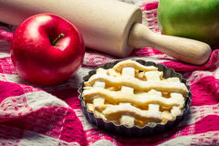 Small apple pie with fruits and a rolling pin Royalty Free Stock Photos