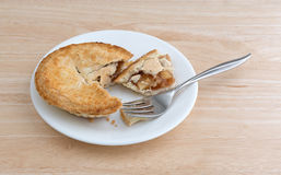 Small apple pie on plate with fork table top Stock Images