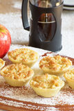 Small apple tarts or tartlets on wood with coffee. Tasty mini apple tarts on wood with coffee and ready to serve Royalty Free Stock Photos