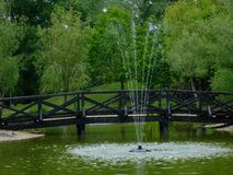 Small arching wooden foot bridge over small green pond. And splashing fountain. bright green trees with lush foliage in the background. outdoors concept. beauty stock image