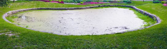 Small artificial ornamental pond in a stone frame. A small artificial decorative pond in a stone frame Stock Photo