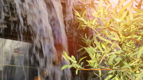 Small artificial waterfall through the green leaves. stock video footage