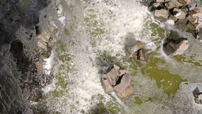 Small artificial waterfall view from the top. Waterfall is flowing down from above on big stones. stock video footage