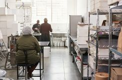 Small artisanal chocolate making factory with people working. African workers preparing packaging and ingredients while working together in an artisanal stock image