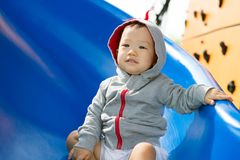 Small Asian baby boy playing slide. Small baby boy spending time outdoor on slide Stock Photography