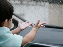 Small Asian baby girl`s hands trying to catch the rain falling down onto a car windshield. Small Asian baby girl`s hands reaching out and trying to catch the Royalty Free Stock Photography