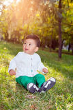 A small asian child plays in the Park sitting on the grass Royalty Free Stock Photography