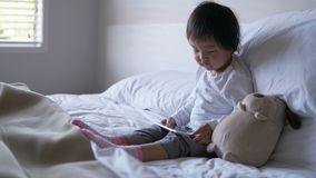 Small Asian chinese toddler sitting on the bed addicted to ipad stock photos