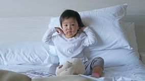 Small Asian chinese toddler sitting on the bed early morning. In a daze Royalty Free Stock Image