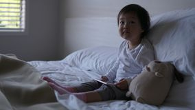 Small Asian chinese toddler sitting on the bed with ipad. Small Asian chinese toddler sitting on the bed addicted to iPhone and looking up Stock Images