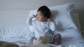 Small Asian chinese toddler sitting on the bed puzzled. From just waking up Royalty Free Stock Photography