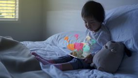 Small Asian chinese toddler sitting on the bed with special effects from ipad. Small Asian chinese toddler sitting on the bed addicted to iPhone and special Royalty Free Stock Images